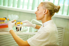 Medical doctor woman looking on test tube with blood Stock Photos