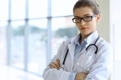 Medical doctor woman over clinic interiers background Stock Image