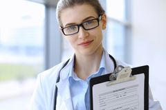 Medical doctor woman over clinic interiers background Royalty Free Stock Images