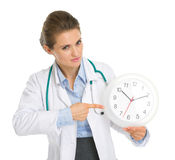 Medical doctor woman pointing on clock. Isolated on white Royalty Free Stock Photos