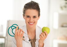 Medical doctor woman showing apple and stethoscope. Happy medical doctor woman showing apple and stethoscope Royalty Free Stock Photography
