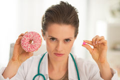 Medical doctor woman showing donut and pill Royalty Free Stock Photos