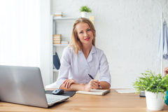 Medical doctor woman sitting at desk in medical Stock Image