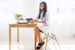 Medical doctor woman sitting at desk and working stock images