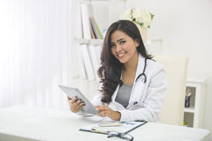 Medical doctor woman with stethoscope using tablet pc Stock Photos