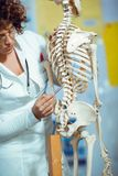 Medical doctor woman teaching anatomy using human skeleton Royalty Free Stock Image