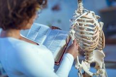 Medical doctor woman teaching anatomy using human skeleton. Model Royalty Free Stock Image