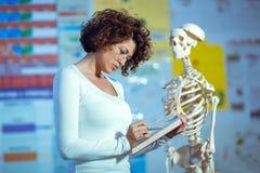 Medical doctor woman teaching anatomy using human skeleton. Model Stock Images