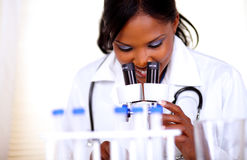 Medical doctor woman working with a microscope stock photo