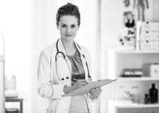 Medical doctor woman writing in clipboard Stock Images