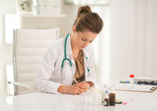 Medical doctor woman writing prescription Stock Image