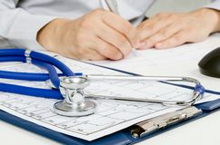 Medical doctor working at desk. Close up of stethoscope Royalty Free Stock Photo