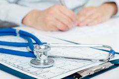 Medical doctor working at desk. Close up of stethoscope Royalty Free Stock Photography