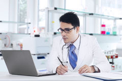 Medical doctor writes prescription in laboratory Stock Image