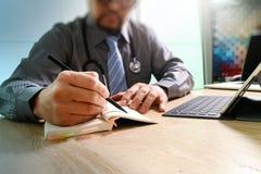 Medical doctor writing on notebook and digital tablet docking ke Royalty Free Stock Images