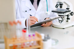 Medical doctor writing something in clipboard Stock Image