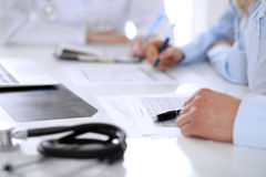 Medical doctor and young couple patients discussing something at the table . Hands close-up Stock Images