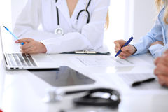 Medical doctor and young couple patients discussing something at the table . Hands close-up Stock Photography