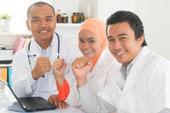 Medical doctors celebrating success. Successful medical doctors celebrating success inside hospital room. Southeast Asian Muslim people Royalty Free Stock Photo