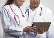 Medical doctors controlling tablet pc Royalty Free Stock Photos