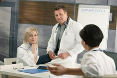 Medical doctors discussing diagnosis. Sitting in doctor's room stock photo