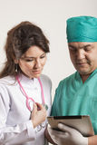 Medical doctors looking at tablet Stock Photo