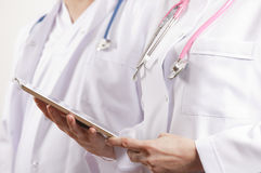 Medical doctors looking at tablet Stock Images