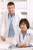 Medical doctors at office. Medical doctors working in team at office, smiling. Focus on female stock photos