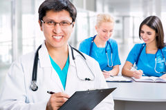 Medical doctors. Portrait of a smart male doctor sitting in front of his team and smiling Stock Photography
