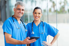 Medical doctors tablet pc. Two medical doctors using tablet pc in hospital stock photo