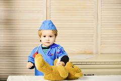 Medical education and childhood concept. Kid in doctor coat. Makes injection to teddy bear. Boy in surgical uniform holds syringe on wooden background stock photos