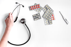 Medical equipment with stethoscope and pills in doctor`s office on white desk background top view mock-up Royalty Free Stock Photography
