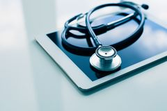 Medical equipment on table. Blue stethoscope and tablet stock images