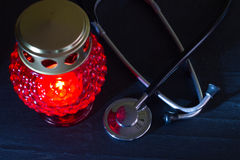 Medical error mistake concept with stethoscope and cemetery candle Royalty Free Stock Image