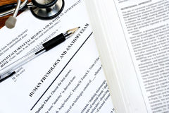 Medical Exam. Papers on a desk with a pen, part of a stethoscope and a medical book.  Concept of Royalty Free Stock Photography