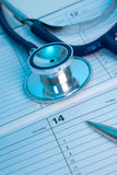 Medical exam planning. Planning routine medical exam represented by part of stethoscope, calendar and pen. Family doctor workplace Royalty Free Stock Photography