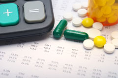 Medical expenses. Calculator and pills on account paper background Royalty Free Stock Images