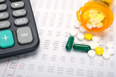Medical expenses analysis. Calculator and pills on account paper background Royalty Free Stock Photos