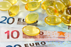 Medical expenses concept. Yellow pills and euro currency Royalty Free Stock Photography