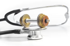 MEDICAL EXPENSES 3. A stethoscope with a euro-coin-weight-lift on top Stock Image