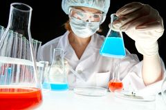 Medical experiment. Laboratory worker looking at bottle with liquid during scientific experiment in laboratory royalty free stock photography