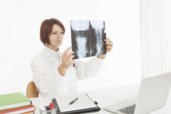 Medical expert looking at x-ray scan while sitting at desk Stock Photos