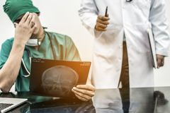Doctor covering his face with hand. Medical Failure Concept - Surgical doctor covering his face with hand face palm expressing disappointment while holding xray Royalty Free Stock Images