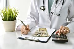 Medical fee, Health insurance, Doctor writing medication note and calculate the examination charges in hospital. Medical fee, Health insurance, Doctor writing stock images