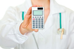 Medical female doctor holding calculator. Close-up Stock Photos