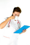 Medical female doctor with stethoscope and clipboard drinking co Stock Photo