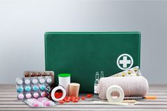 First aid kit with medical supplies on wooden. Medical first aid first aid kit medical supplies white background healthcare and medicine still life Stock Image