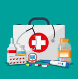 Medical first aid kit with pills and devices. Medical first aid kit with different pills, phonendoscope and thermometer, healthcare. Vector illustration in flat Stock Image