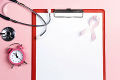 Medical folder with pink ribbon, stethoscope and alarm clock on stock photography
