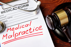 Medical form with words Medical Malpractice. And gavel royalty free stock photos